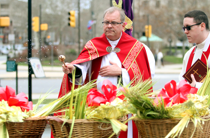 Father Dennis Gill, rector of Cathedral Basilica of SS. Peter and Paul, blesses the palm across from the Cathedral in Sister Cities Park.