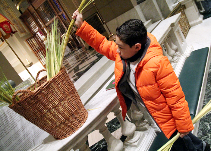 Josue Alegre gets palm for his family before Mass.
