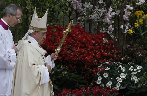 Pope Francis leaves after celebrating Easter Mass in St. Peter's Square at the Vatican April 5, 3015. Thousands of bushes, flowering trees, tulips and other flowering bulbs, which are a gift of growers in the Netherlands, will be replanted in the Vatican gardens. (CNS photo/Paul Haring)