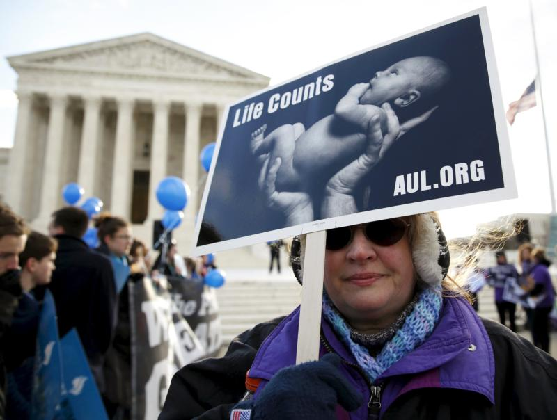 A pro-life supporter holds up a sign in front of the U.S. Supreme Court in Washington March 2 on the morning the court heard oral arguments in a challenge to a Texas law imposing new standards on abortion clinics and requiring abortion doctors to have hospital admitting privileges. (CNS photo/Kevin Lamarque, Reuters)