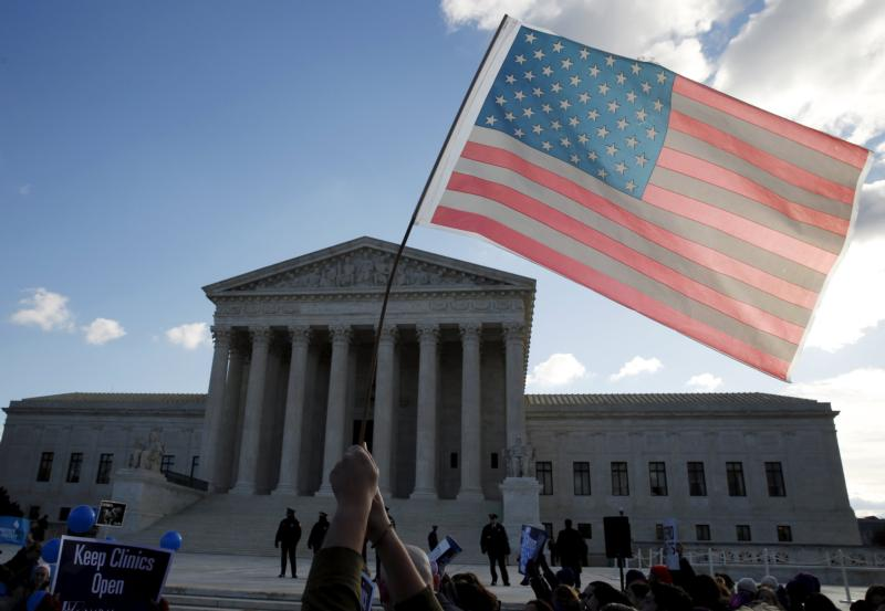 A person holds up the American flag in front of the U.S. Supreme Court in Washington March 2. (CNS photo/Kevin Lamarque, Reuters)