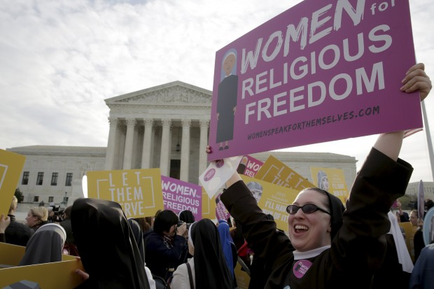 A religious sister displays a sign as she and others protest the Affordable Care Act's contraceptive mandate March 23  outside the U.S. Supreme Court in Washington. The court heard oral arguments in the Zubik v. Burwell mandate case. (CNS photo/Joshua Roberts, Reuters)