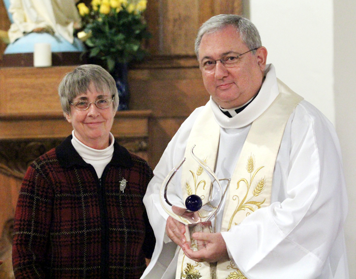 Sr. Donna Breslin presents Father Wayne Paysse with the SKD National Justice Award during her feastday celebration.