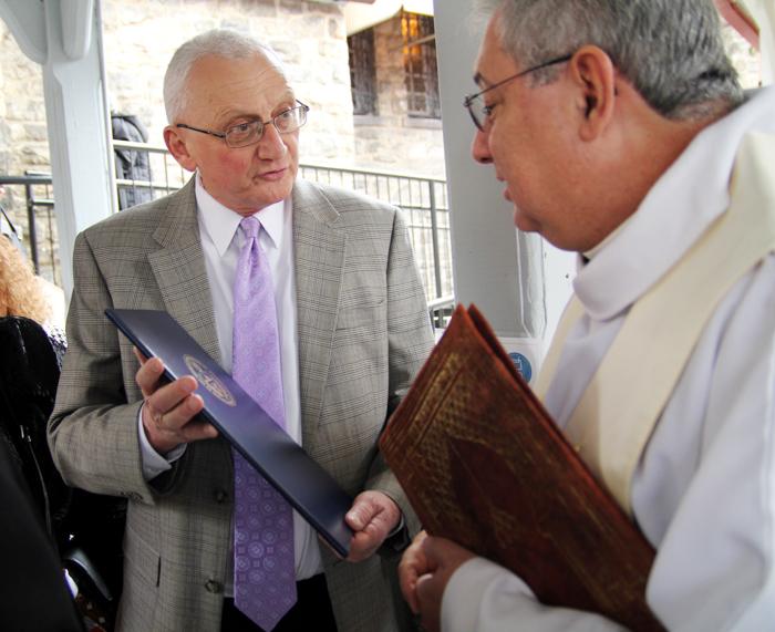 State representative Gene DiGirolamo presents awardee Father Wayne Paysse with a proclamation.