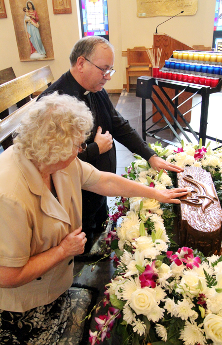 Irena Jankowski and Father Tadeusz Gorka pray before the relic of St. Sharbel Makhlouf at St. Maron Church in South Philadelphia, where the relic was displayed fopr veneration from March 11-13. (Sarah Webb)