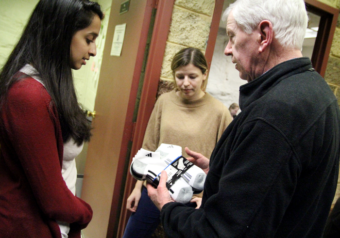 Tom Costello, right, founder of The Joy of Socks, chats with volunteer medical students Nirali Butala (left) and Meredith LaRose at Our Brother's House. (Sarah Webb)