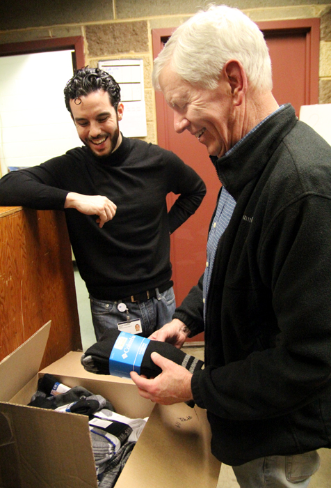 Gerald Gibbons, left, director of JeffHOPE Clinic at Our Brother's House, is glad to receive two full boxes of socks that Tom Costello delivers as part of The Joy of Socks, the charitable organization he founded. (Sarah Webb)