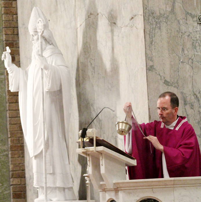 Msgr. Joseph McLoone reads the Gospel during the Saint Patrick Mass on March 13th.