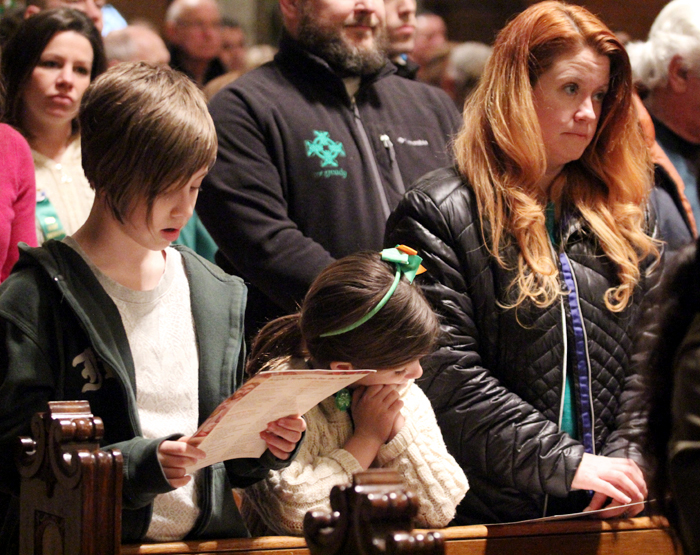 Charolotte, Lily and Julia McGeady attend Mass before the Saint Patrick Day Parade.