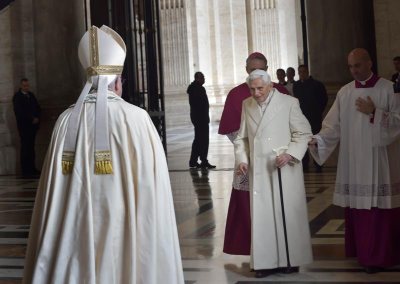 "Retired Pope Benedict XVI prepares to greet Pope Francis during the opening of the Holy Door of St. Peter's Basilica at the Vatican in this Dec. 8, 2015, file photo. In a written interview, the retired pope commented on the theme of mercy. ""Mercy is what moves us toward God, while justice makes us tremble in his sight, Pope Benedict said. (CNS photo/Stefano Spaziani, pool)"