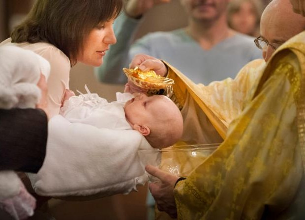 Oksana Vydash holds on to her goddaughter Veronika Victoria Shalai during her baptism at St. Mary's Assumption Ukrainian Catholic Church in St. Louis in this Jan. 12, 2013, file photo. (CNS photo/Lisa Johnston, St. Louis Review)
