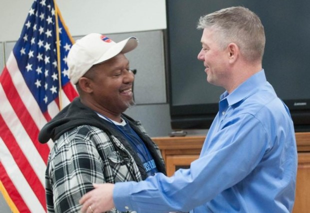 Deacon John Krenson, right, congratulates Bobby King Feb. 29 for completing the transitional housing program, finding a job and moving out on his own in Nashville, Tenn. (CNS photo/Theresa Laurence, Tennessee Register)