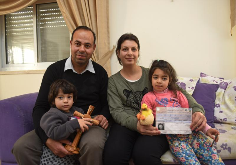 Nicola Sansour and his wife, Nivine, pose with two of their children, Elia, 2, and Rivana, 5, at their home in Beit Jalla, West Bank, March 24. Nivine Sansour is holding her permit from the Israelis to travel to Jerusalem for Holy Week, but Nicola Sansour did not receive Israeli permission to travel to Jerusalem. (CNS photo/Debbie Hill)