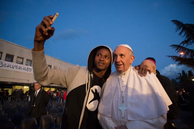 Pope Francis poses for a selfie with a man after Holy Thursday Mass of the Lord's Supper at the Center for Asylum Seekers in Castelnuovo di Porto, about 15 miles north of Rome March 24. The pope washed and kissed the feet of refugees during the Mass. (CNS photo/L'Osservatore Romano, handout)