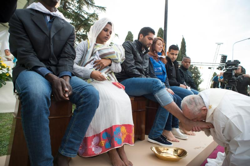 Pope Francis kisses the foot of a refugee during Holy Thursday Mass of the Lord's Supper at the Center for Asylum Seekers in Castelnuovo di Porto, about 15 miles north of Rome March 24. The pope washed and kissed the feet of refugees, including Muslims, Hindus and Copts. (CNS photo/L'Osservatore Romano, handout)