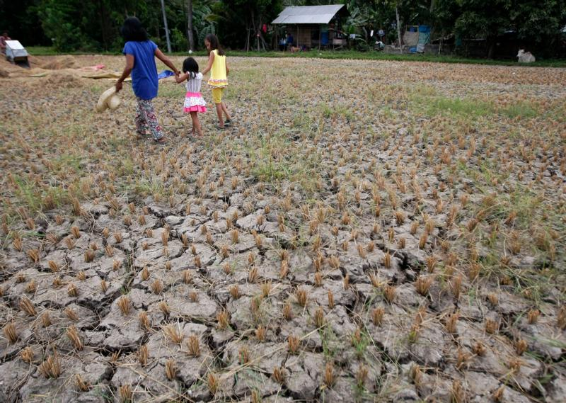 A woman and children walk through a drought-stricken rice field April 3 in Cebu, Philippines. Short-term goals on climate change must become long term solutions, said Ghanaian Cardinal Peter Turkson, president of the Pontifical Council for Justice and Peace. (CNS photo/Jay Rommel Labra, Reuters)