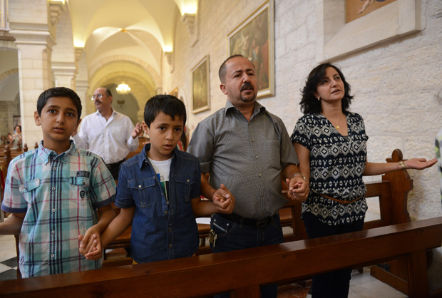 "A family prays in 2014 in the Church of St. Catherine in Bethlehem, West Bank. Pope Francis' postsynodal apostolic exhortation on the family, ""Amoris Laetitia"" (""The Joy of Love""), was released April 8. The exhortation is the concluding document of the 2014 and 2015 synods of bishops on the family. (CNS photo/Debbie Hill)"