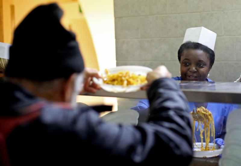 Cecile Kyenge, Italian minister for integration,  serves food in the kitchen of the Astalli Center of the Jesuit Refugee Service in 2013 in Rome. Just months after his election that year, Pope Francis had said church buildings that no longer house nuns, friars, monks and other religious should be used to shelter refugees. (CNS photo/Alessandro Di Meo, EPA)