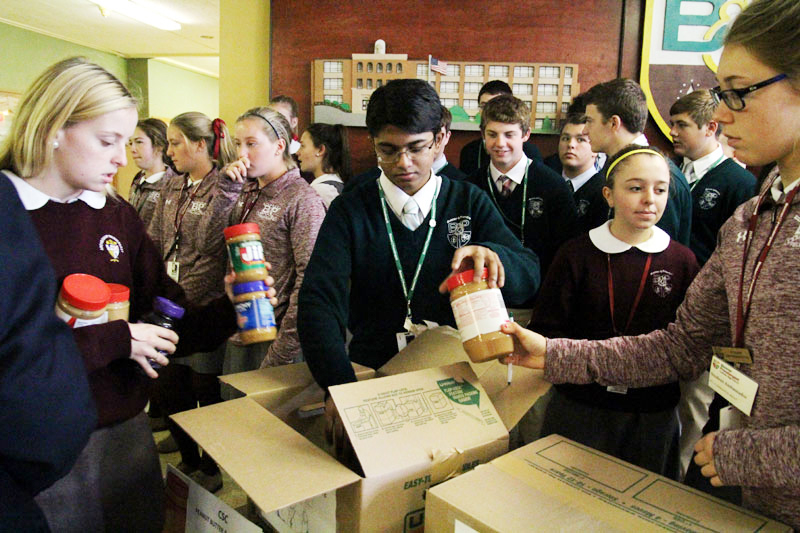 Monsignor Bonner-Archbishop Prendergast High School students box up the peanut butter and jelly they collected for the annual Peanut Butter and Jelly Drive run by archdiocesan Nutritional Development Services on Nov. 2, 2015. A new Pew Research Center study of Americans across the religious spectrum finds that 65 percent of highly religious adults say they have donated money, time or goods to help the poor in the past week, more than half again as many as the 41 percent who are less religious.