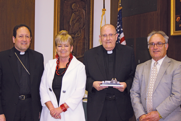 Father Anthony Orth (center right), Catholic Social Services' Volunteer of the Year, receives his award April 15 at the Archdiocesan Pastoral Center from (from left ) Bishop John J. McIntyre; Amy Stoner, CSS director of Community Based and Homeless Services Divisions; and James Amato, secretary of Catholic Human Services of the Archdiocese of Philadelphia.