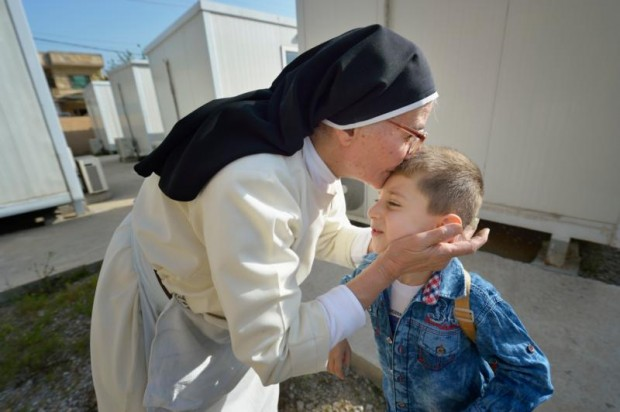 Dominican Sister Elene kisses 4-year old Luis Firas as he walks to a preschool in Ankawa, Iraq, April 7. (CNS photo/Paul Jeffrey)