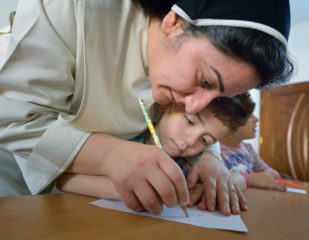 Dominican Sister Ferdos Zora helps a student draw in a preschool for displaced children run by the Dominican Sisters of St. Catherine of Siena in Ankawa, Iraq, April 7. (CNS photo/Paul Jeffrey)
