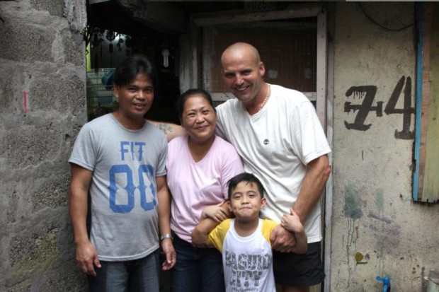 Mark Crosbie poses for a photo with Mel and Merney Macaereg and one of their six children in Manila, Philippines, in this undated photo. Crosbie, an Irish Catholic street cleaner who was filmed for a job-swap TV documentary, has pledged to spend the rest of his life helping the struggling family he lived with in Manila. (CNS photo/courtesy RTE)