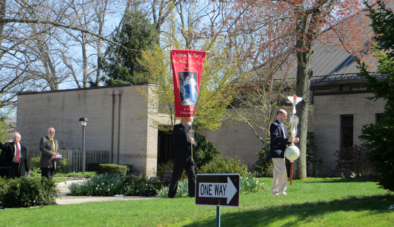 Leading the Legion of Mary procession into St. Eleanor Church in Collegeville April 10 is a man raising the Legion of Mary vexilium, named after the military standard used by units of the ancient Roman army.