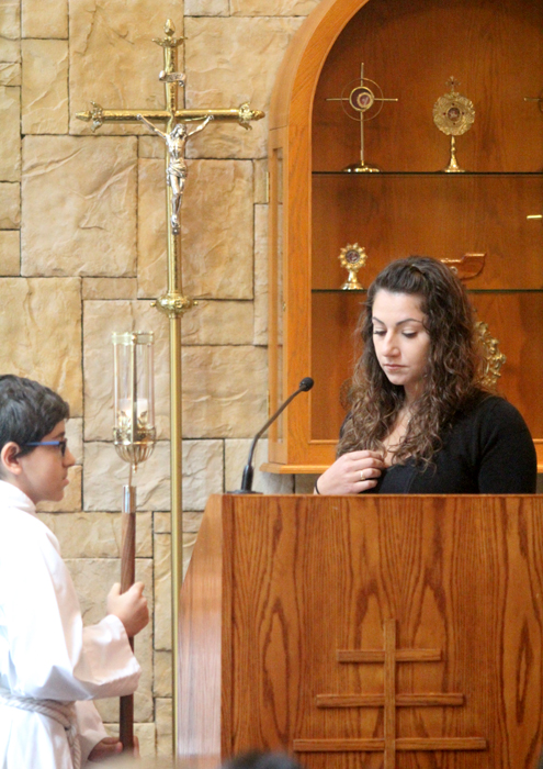 Nahi Rai blesses herself before reading during mass.