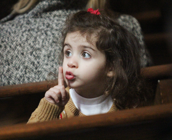 During Mass at St. Maron Church in Philadelphia, Christelle Matar lets her father know she is being quiet. (Sarah Webb)