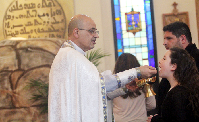 Katie Akkari recives communion from Father Vincent Farhat.