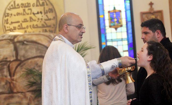 Katie Akkari recives communion from Father Vincent Farhat.