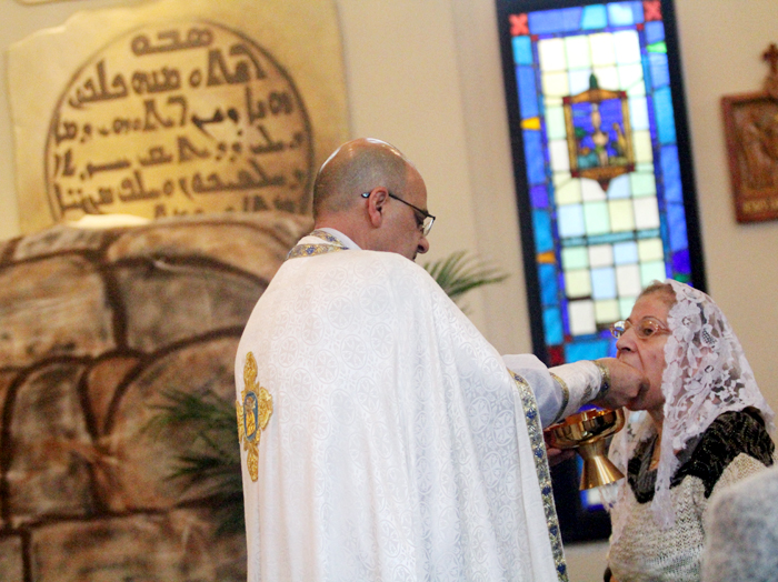 Father Vincent Farhat distributes communion to Alice Raai.
