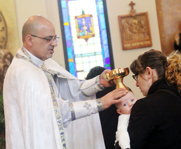 Father Vincent Farhat blesses Jacob Sudano as his mother Rola Dakour prepares to recive Holy Communion.