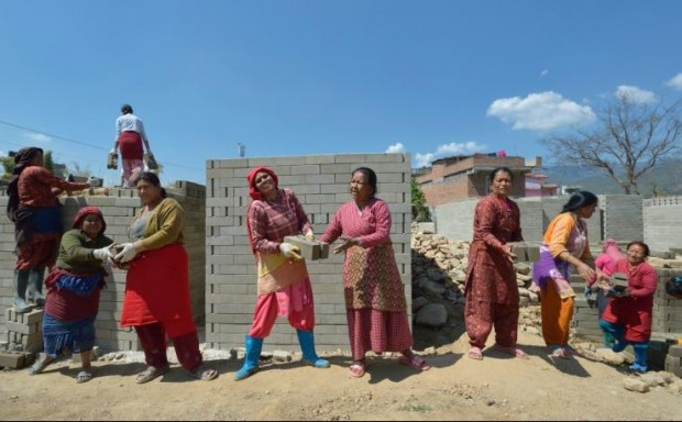 Women in Sanogoan, Nepal, stack blocks that will be used to build new homes in this March 15 photo. April 25 marks the one-year anniversary of the magnitude-7.8 earthquake that struck the Himalayan nation, killing more than 9,000 people. (CNS photo/Paul Jeffrey)