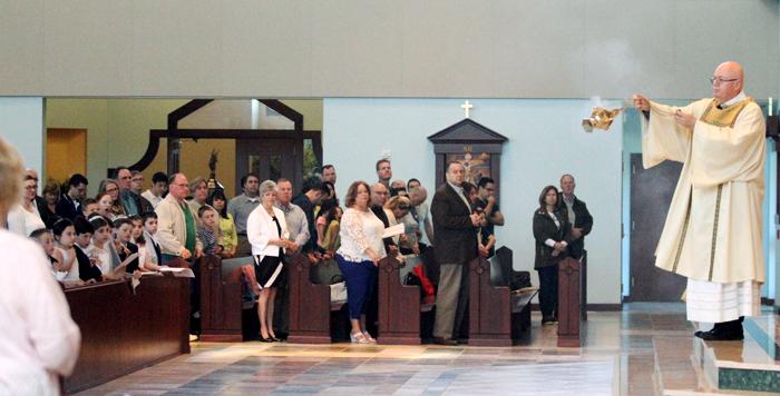Deacon Robert Brady incences the congregation.