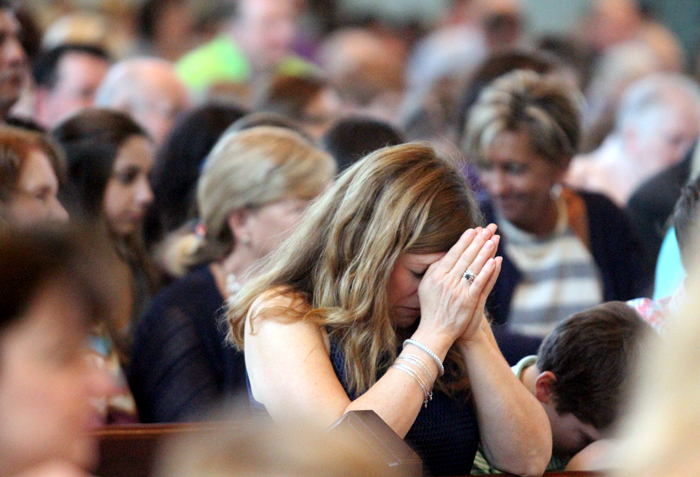 Kelly Parisi prays during Liturgy of the Eucharist.