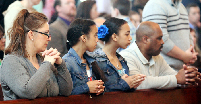 Tina, Alaire, Aceline and Dominique Galloway pray together.