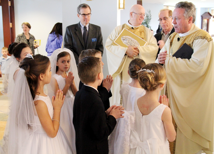Msgr. Joseph Gentili gives words of encouragment to the 2nd graders before the mass where they will receive their first Holy Communion.