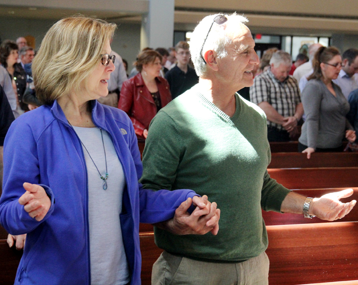 Lynn and Sam Iosorelli hold hands as they pray the Lord's Prayer.