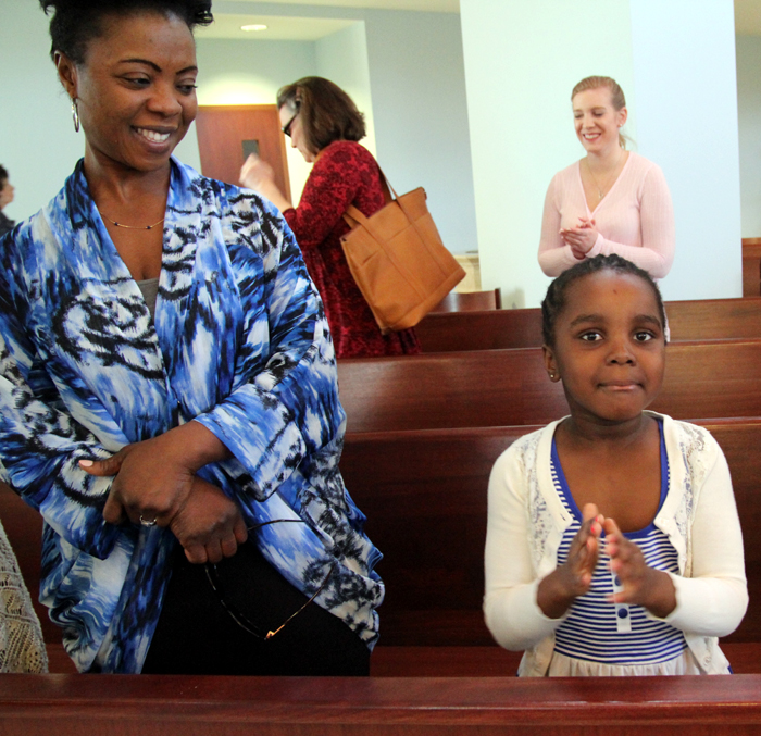 Madeleine Soumaoro applauds the children that received holy communion for the first time.