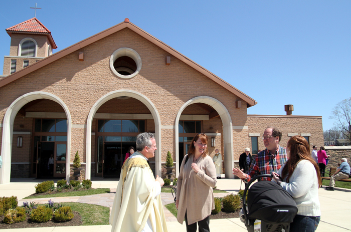 Msgr. Joseph Gentili chats with Brooks, Russell, Julia and Isabella Palmer after mass.