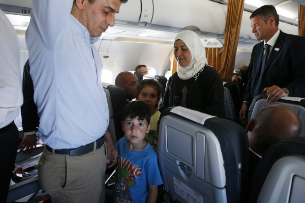 Syrian refugees walk though the aisle of Pope Francis' flight from the Greek island of Lesbos to Rome April 16, 2016. The pope concluded his one-day visit to Greece by bringing 12 Syrian refugees to Italy aboard his flight. (CNS photo/Paul Haring)