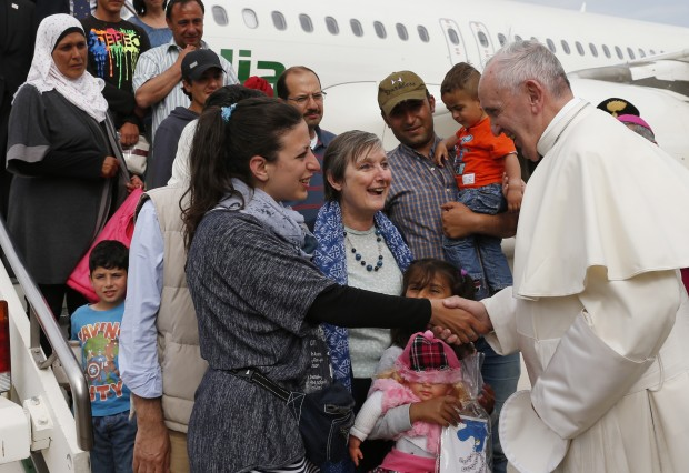 Pope Francis greets Syrian refugees he brought to Rome from the Greek island of Lesbos, at Ciampino airport in Rome April 16, 2016. The pope concluded his one-day visit to Greece by bringing 12 Syrian refugees to Italy aboard his flight. (CNS photo/Paul Haring)