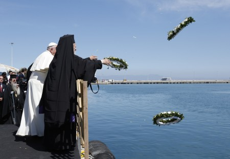 Pope Francis, Patriarch Bartholomew and Archbishop Ieronymos (not visible) throw wreaths into the sea during a service in memory of migrants who have died trying to reach Europe, on the island of Lesbos, Greece, April 16, 2016. (CNS photo/Paul Haring)