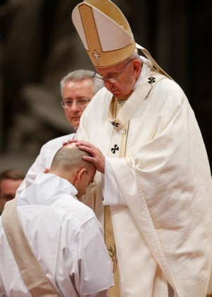 Pope Francis ordains one of 11 priests during a Mass in St. Peter's Basilica at the Vatican April 17. Nine were ordained for the Diocese of Rome and two for the Rogationist religious order. (CNS photo/Paul Haring)