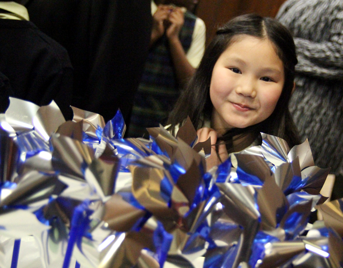Justine Weng, third grade student at St. Francis De Sales School, is one of more than 150 studetns to plant her pinwheel for Child Abuse Awareness Month.