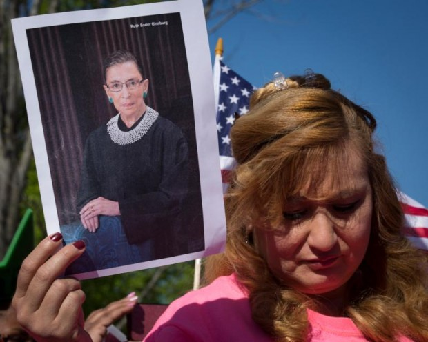 A demonstrator holds a photo of Justice Ruth Bader Ginsburg while she stands outside the U.S. Supreme Court in Washington April 18 as inside the justices hear oral arguments in a challenge by several states to President Barack Obama's deferred deportation programs. (CNS photo/Tyler Orsburn)