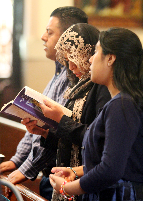 Alfonso Pantoja, Laticia Justo and Maria Pantoja pray during the 11:30a.m. Spanish mass at St. Michael Church in West Kensington section of Philadelphia.
