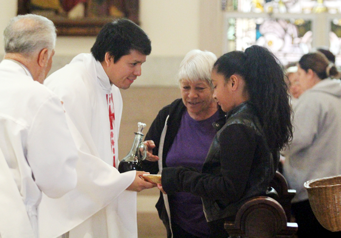 Carmen Ortiz and Karina Valdez present the bread and  wine to Father Arturo Chagala.